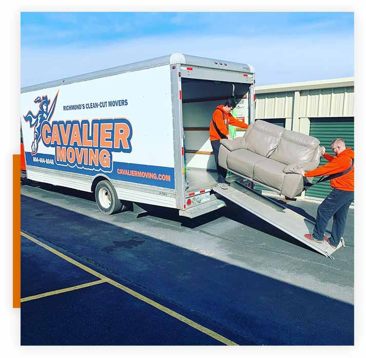 This image shows a Cavalier Moving crew loading a sofa into a moving truck.